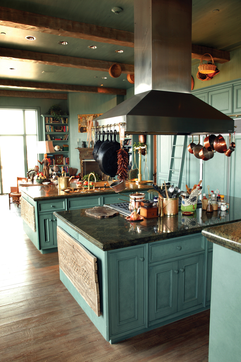 Three large islands serve as the kitchen's central axis. With its French farmhouse details, such as old plank floors from a barn, wooden ceiling beams, and distressed cabinets, the kitchen is warm and inviting.