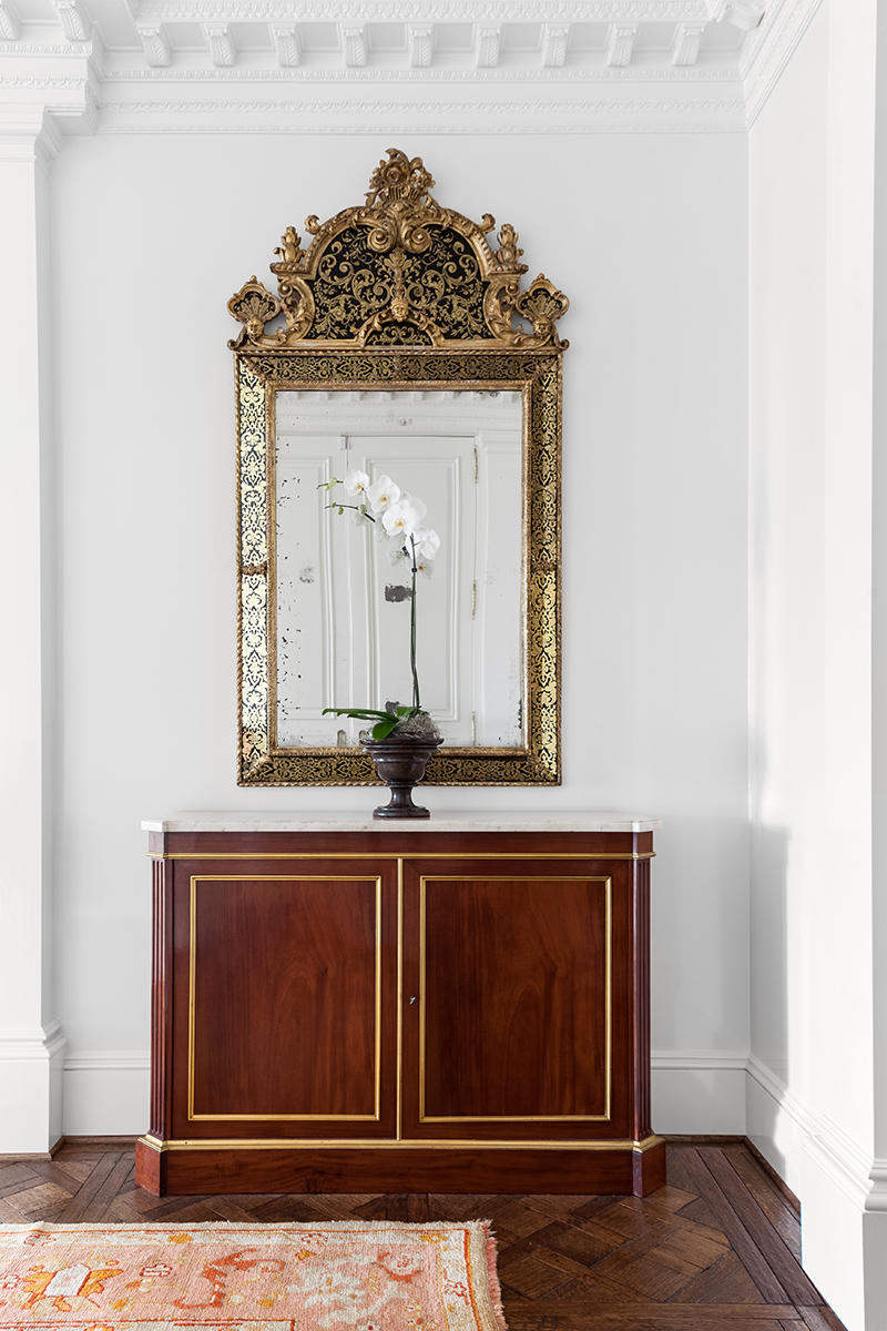 Sara's antique cabinet and gilt mirror were repurposed in the apartment's entryway.