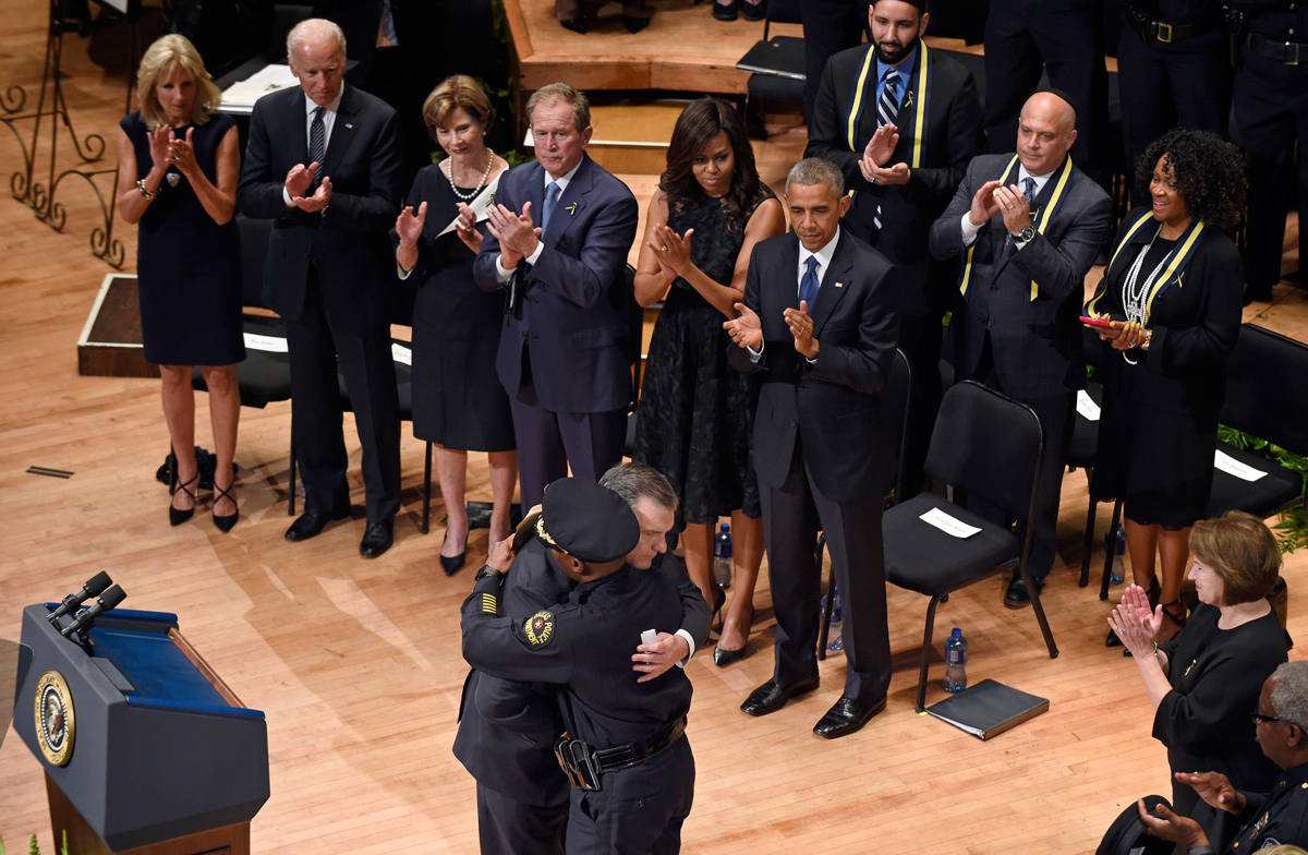Chief David Brown and Mayor Mike Rawlings embrace at an interfaith memorial service held at the Morton H. Meyerson Symphony Center a few days after the attack.