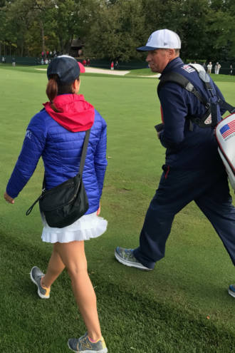 """Julie Fox walking the course with Phil Mickelson's caddy, Jim """"Bones"""" Mackay."""