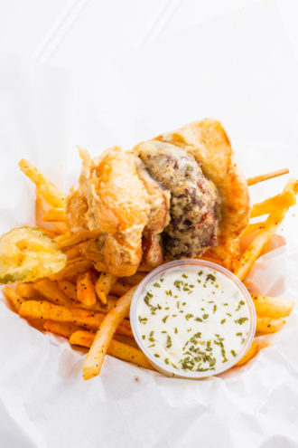 The Deep Fried Bacon Burger Dog Slider on a Stick is served with ranch dressing, fries, and a fried pickle.