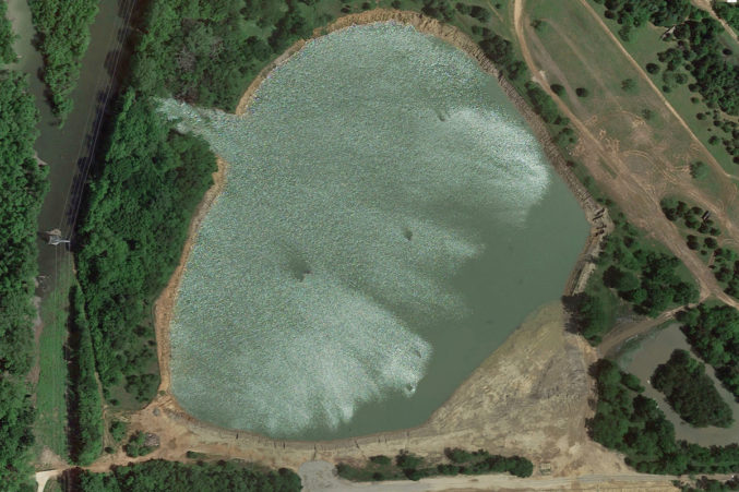3. By April 2016, the pit had filled and breached a wall (10 o'clock position), pouring possibly contaminated water into the Trinity floodplain, a serious issue for the EPA and the TCEQ.