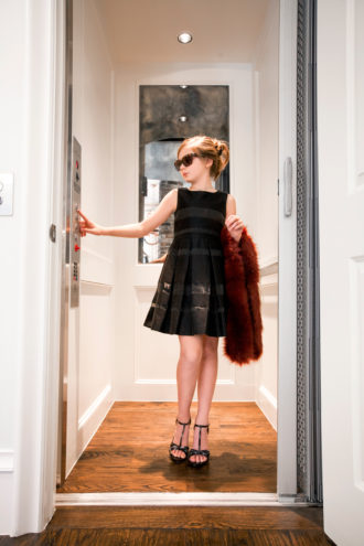 Cameron is having a total Audrey Hepburn moment as she steps into elevator wearing a classic, black dress, sophisticated sunglasses, and a faux fur stole