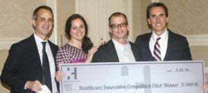 Socrates accepts a check after winning the inaugural Health Innovation Pitch Competition. (Quincy Preston/Dallas Innovates)