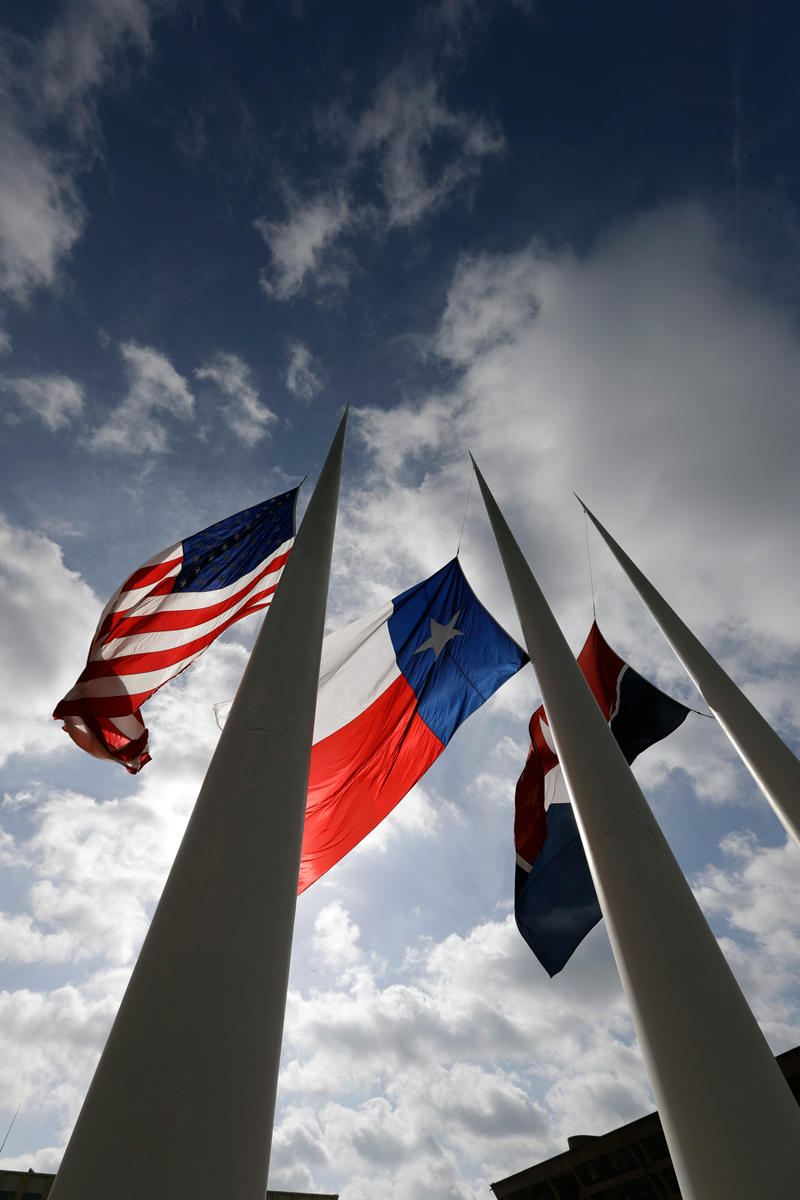 The flags at Dallas City Hall flying at half-mast for the fallen police officers. Other tributes—blue ribbons, banners, t-shirts—appeared all over the city in the wake of the shooting.