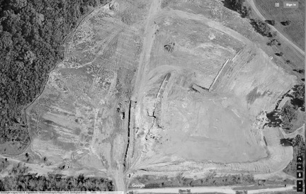 Borrow Area A is located at the western end of Elam Road, adjacent to the Trinity Forest Golf Club. To the left of the central road, one truck can be seen operating a dragline, and another, hauling excavated materials offsite. More recent aerial photos show the pit full of water. (Image: Google Maps)