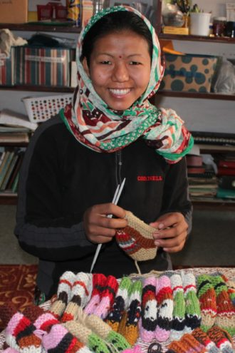 A Nepalese woman knits booties for the 100+ Million exhibit, which is showing at the Fashion Industry Gallery from Feb. 5 to Feb. 10. (Credit: Beverly Hill)