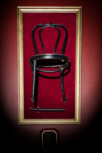 "FOUR DAY WEEKEND'S ORIGINAL STAGE CHAIR: It hangs in the theater, and a plaque beneath it reads: ""This chair was adopted (stolen) from Casa Mañana's Theater on the Square on Four Day Weekend's opening night, February 28, 1997. It has been with us ever since. This chair has appeared in more than 4,000 shows and 25,000 scenes. It has and always will be an original member of the cast. This beloved chair has been a marching band drum, hooker's high heel shoe, crown, canoe, car, airplane, tank, toilet, couch, hospital bed, bagpipe, prison cell, bird cage, angel wing, and countless other memories. Our dependable black chair met its untimely demise in an unfortunate bobsledding accident on January 17, 2015. You are gone but not forgotten. Rest in pieces, old friend."""