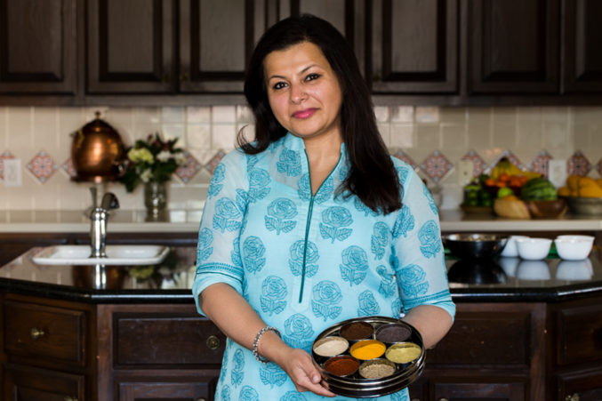 Portrait image of Indian cook Sapna in her home kitchen.