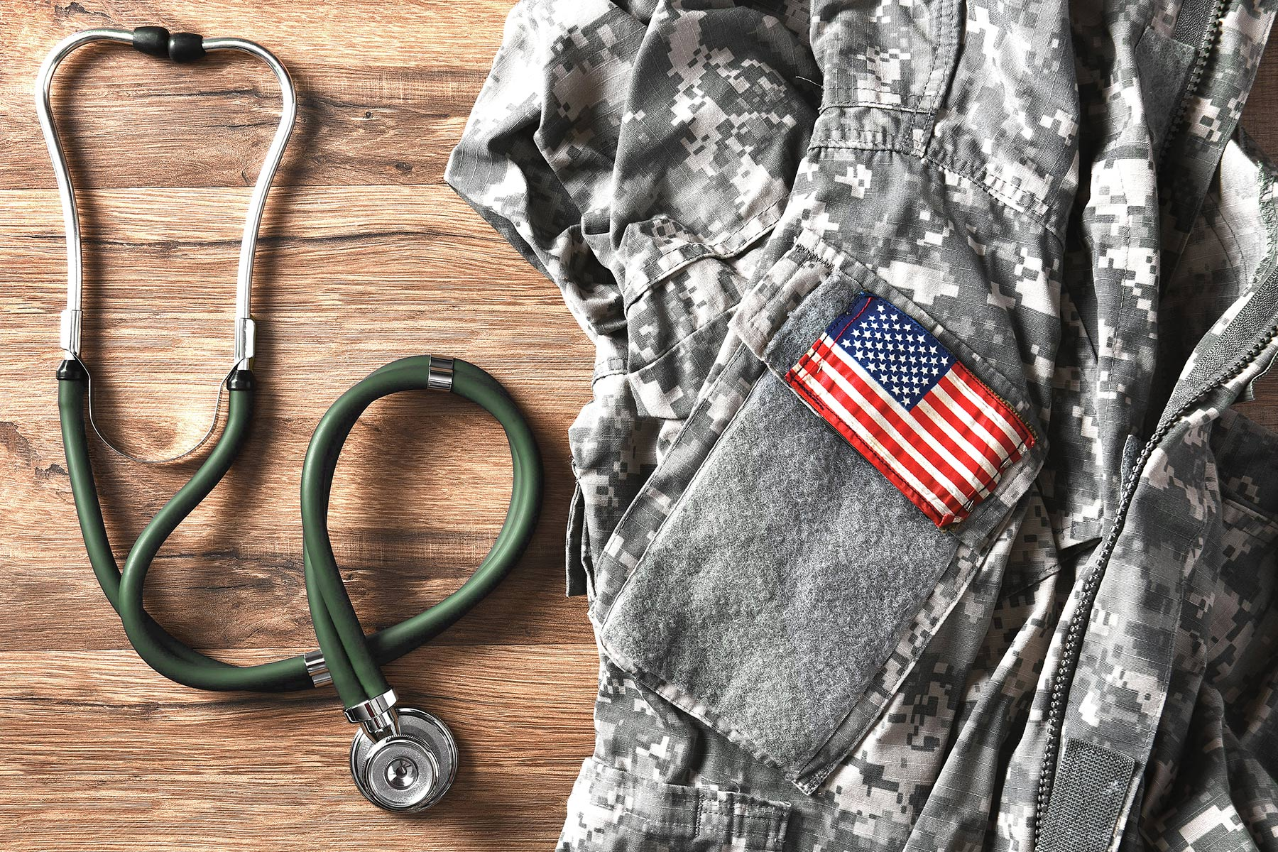 picture of stethoscope next to veteran jacket with American flag patch