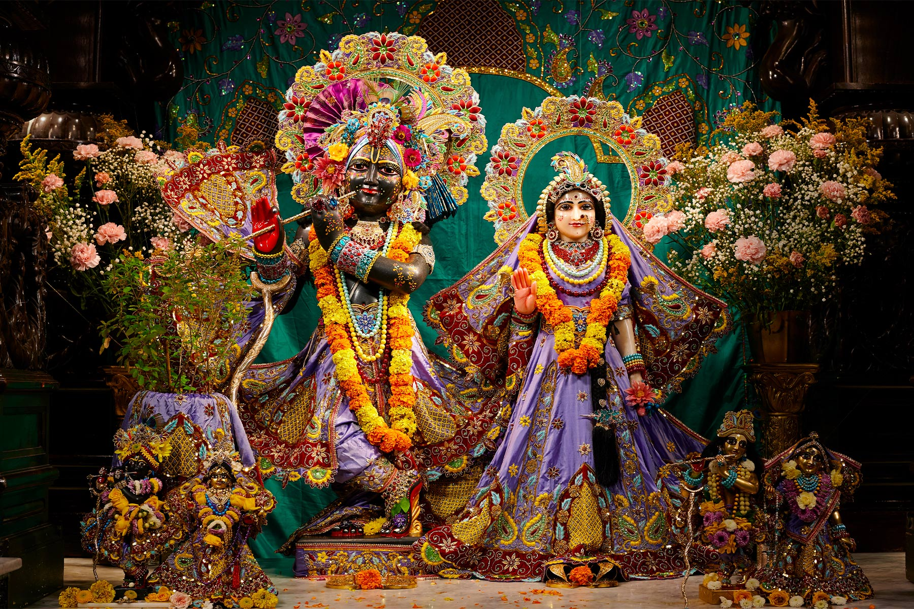 Statues of Krishna and His Female Counterpart Dressed in Purple