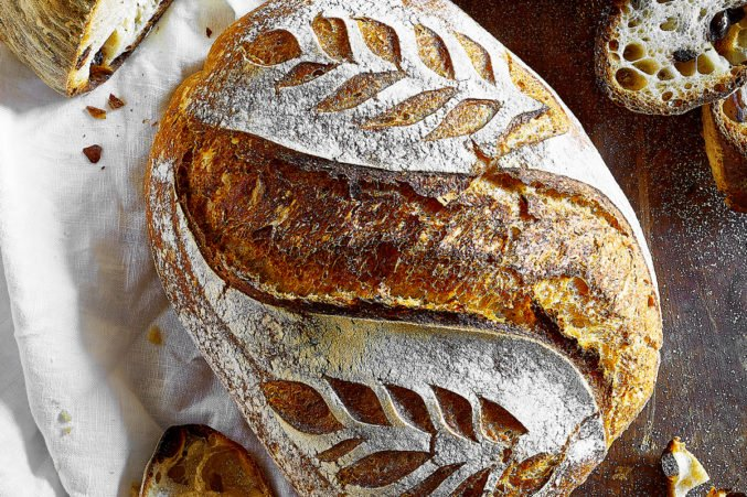 A loaf of rustic sourdough bread with leaf-pattern scoring on the crust.