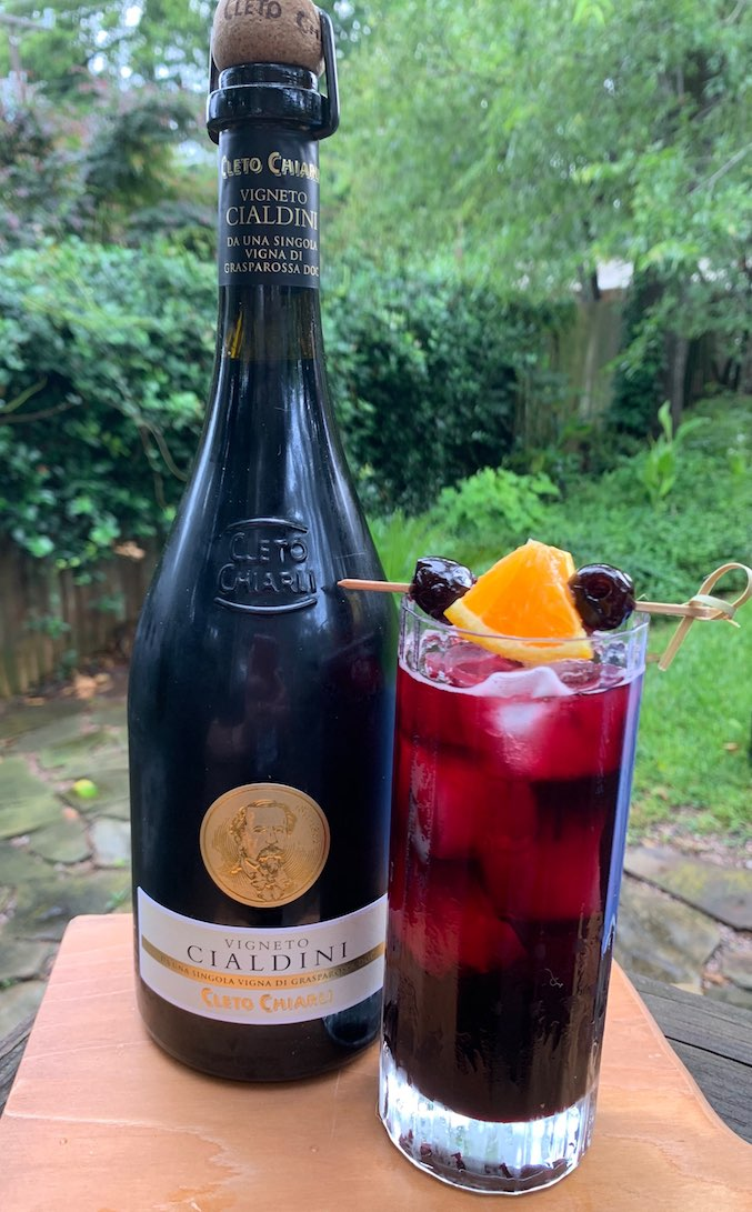 A bottle of lambrusco wine next to a glass of wine spritzer