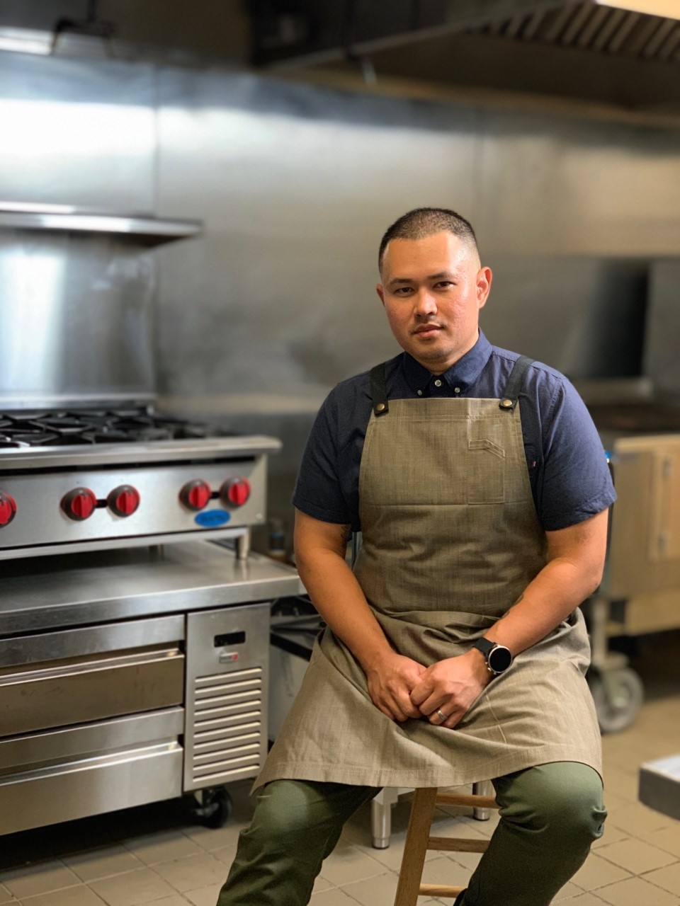Chef Kevin Top sits on a stool inside the commercial kitchen in Plano where he makes his Cambodian food.