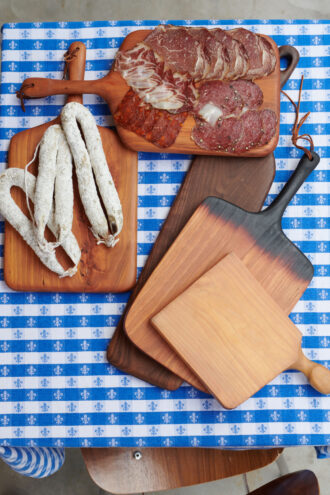 Wood serving boards with charcuterie on top, all spread on a blue and white checkered tablecloth.