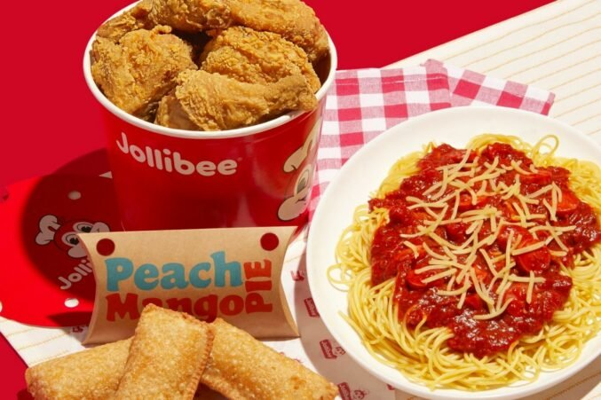 Fast-food spread from Jollibee with a bucket of Chickenjoy fried chicken, mango peach hand pies, and a plate of spaghetti.