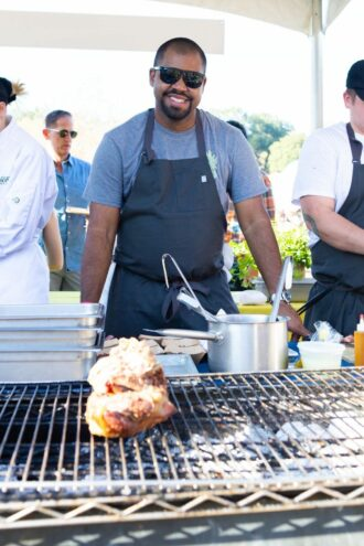 Chef Junior Borges stands in front of a grill at an Austin Food and Wine Alliance food festival.