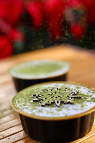 A cup of parfait with a snowflake decal on top, and a dusting of matcha powder.