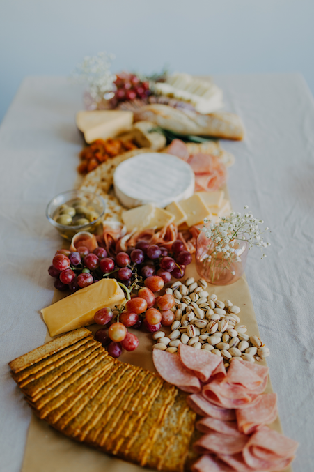 A charcuterie board of cured meats, crackers, and fruit.