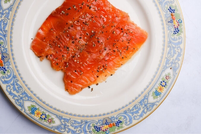 A vibrant orange filet of smoked salmon on a plate with ornate vintage perimeter.