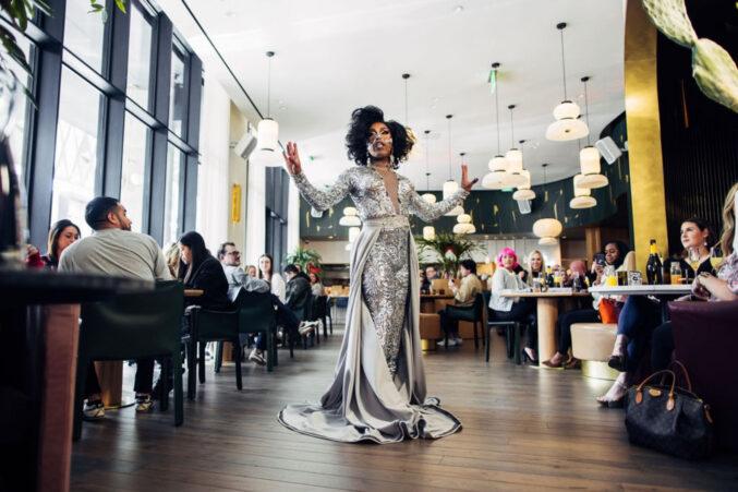 A drag queen in a silver mermaid-silhouette dress.