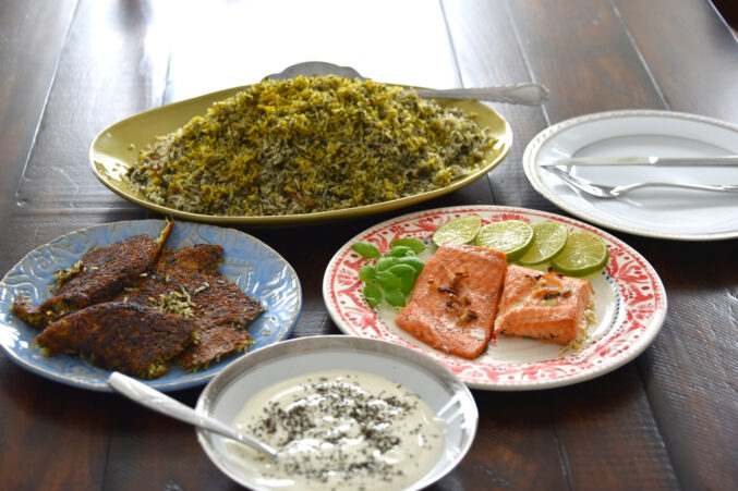 Nowruz traditional foods on a table include herbed basmati rice, white fish fried with citrus, and dill-filled herb sauce.