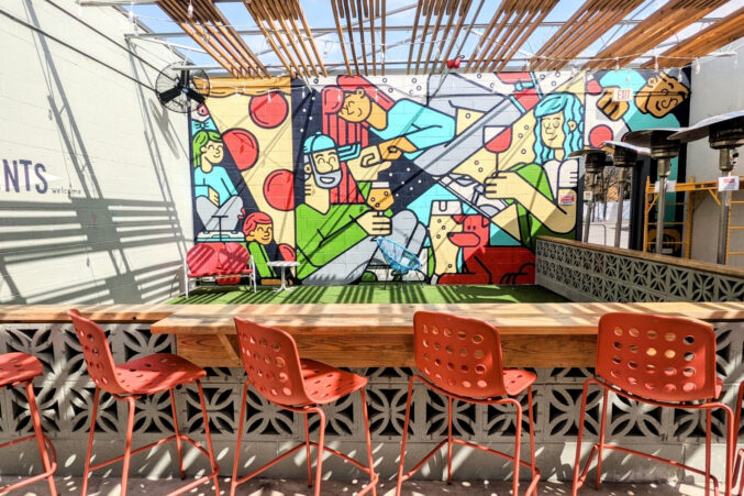 A painted mural with colorful people and pizza at Vector Brewing's outdoor seating space.