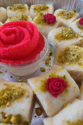 Cheese desserts decorated with bright pink frosting roses.