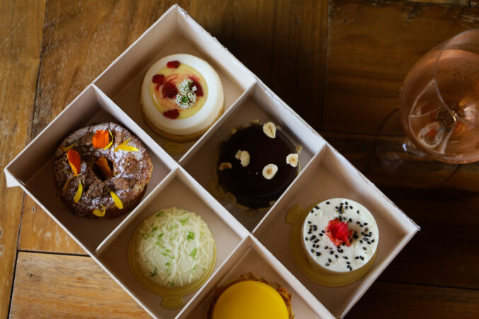 A box with six petite cakes, all different flavors like lemon-raspberry cheesecake and coconut lime.