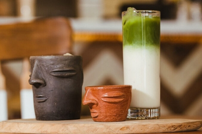 A row of three coffee drinks: horchata in a clay cantarito, espresso in a smaller cantarito, and a tall glass of matcha horchata.