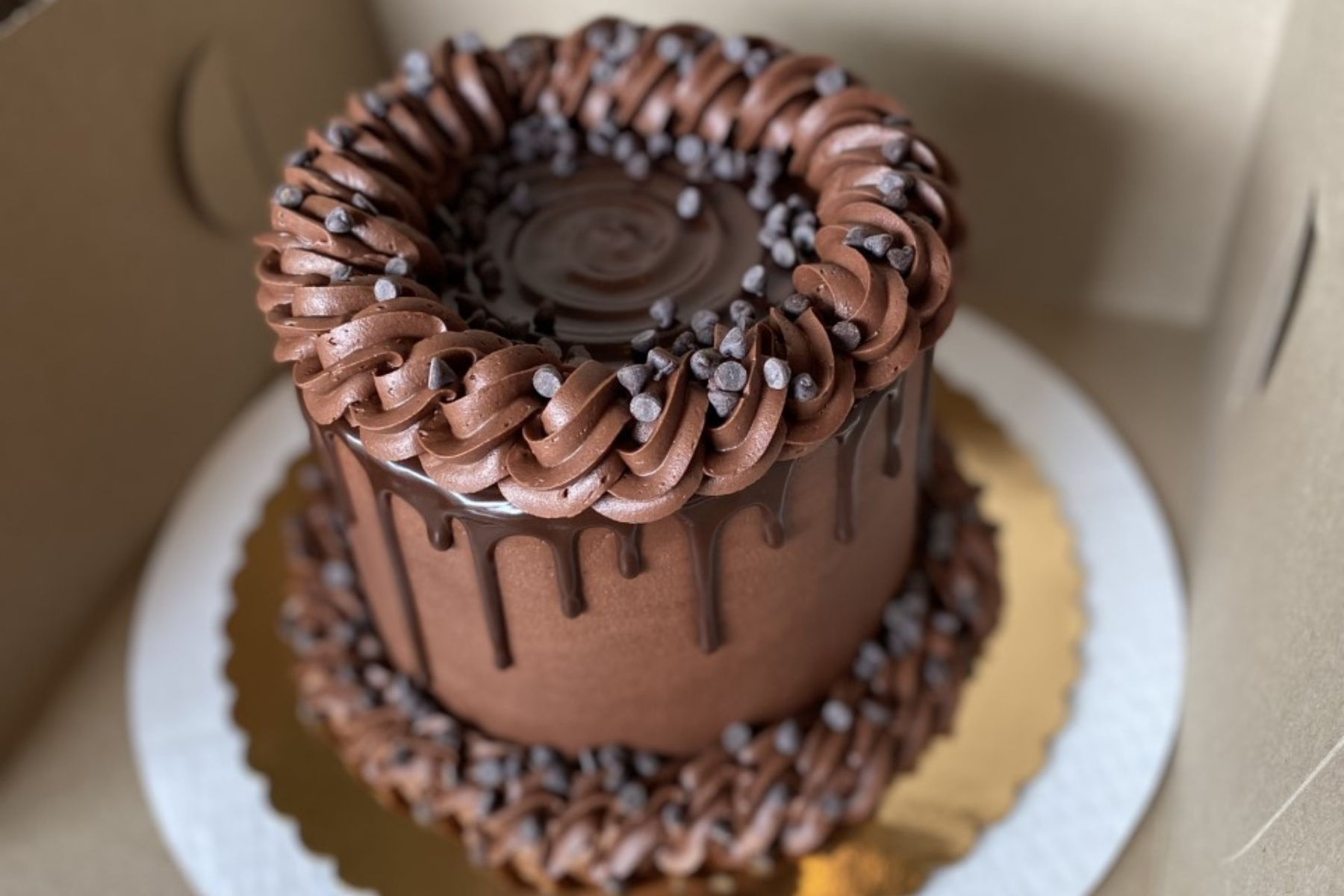 A tall chocolate cake with swirls of frosting and chocolate drizzle.