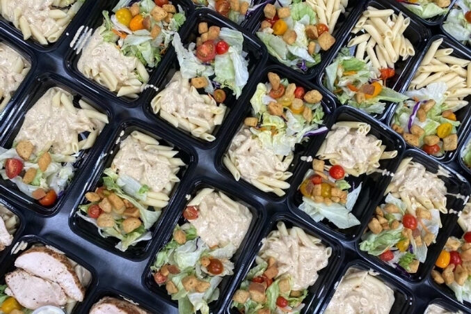 A table full of to-go containers filled with pasta and salad.