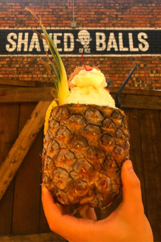 A hand holds up a a hallowed out pineapple that's filled with vanilla ice cream, shaved ice covered in pineapple and coconut syrups. And on top there's whipped cream and a maraschino cherry and tiny umbrella.